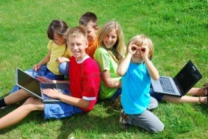 children using laptops outside